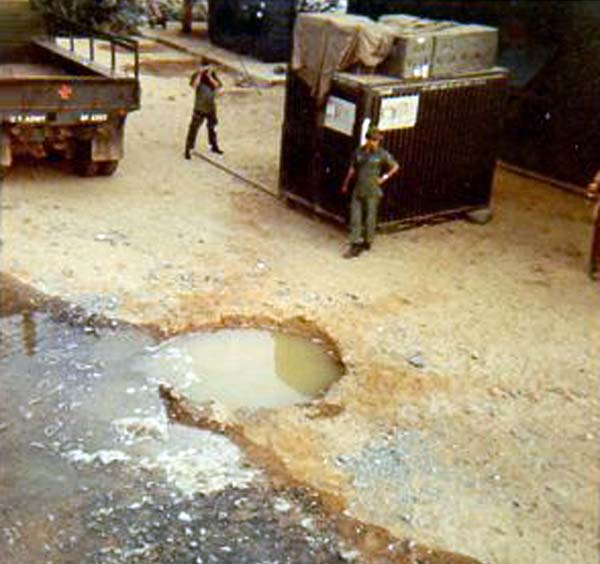 14. Da Nang AB: 366th TFW: Rocket crater at Gunfighter Village and outside my barracks back door. Unrelated to the bomb dump explosions. [Peter Halferty photo].