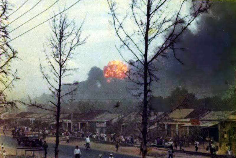 12. Da Nang AB: 366th TFW: Bomb Dump ASP-1 Explosions. Vietnamese civilians near panic, uncertain if the airbase was under attack. Note the foreground trees nearly baren of tree leaves -- Agent Orange effect anyone! April 27, 1968. [Peter Halferty photo].