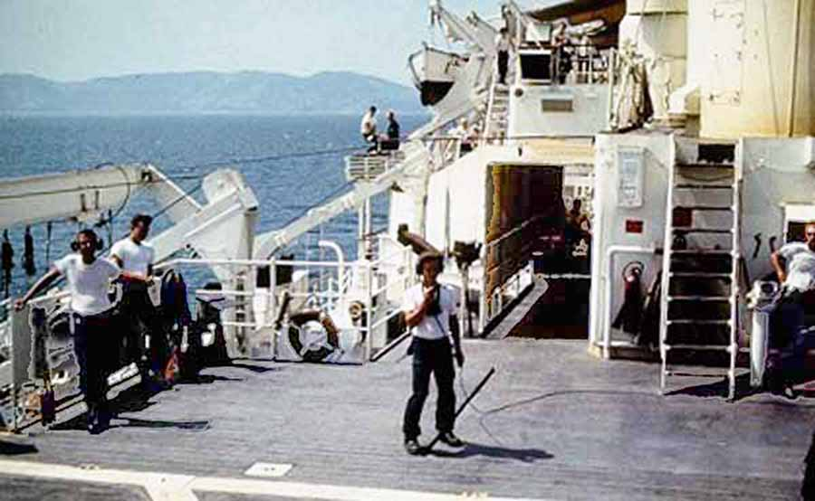 Da Nang Harbor. USS Repose, hospital ship, underway, as deck is cleared and wounded receiving care below.