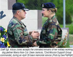 SSgt Alissa Jones accepts the cremated remains of her military working dog partner, Marco, from Col. Dean Jackson, 72nd Mission Support Group commander, during an April 26 [2007] base memorial serive. (Photo by: Dave Faytinger)